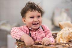 Retrato de um bebê bonito dentro de uma cesta com pão na padaria fotografia de stock