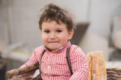Retrato de um bebê bonito dentro de uma cesta com pão na padaria foto de stock royalty free