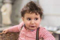 Retrato de um bebê bonito dentro de uma cesta na padaria fotografia de stock