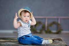Retrato de um bebê bonito em um fundo claro com uma grinalda das flores em sua cabeça que senta-se na cesta do sofá Imagens de Stock