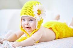 Retrato de um bebê bonito no chapéu amarelo e nas calças que encontram-se para baixo na Fotografia de Stock Royalty Free