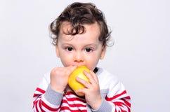Retrato de um bebê bonito que come uma maçã Foto de Stock