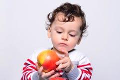 Retrato de um bebê bonito que come uma maçã Fotografia de Stock Royalty Free