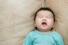 Retrato de um bebê de grito em um backgr de couro Fotografia de Stock
