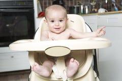 Retrato de um bebê feliz na cozinha do cadeirão Foto de Stock