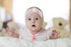 Retrato de um bebê novo bonito que veste uma camisa do bodysuit que encontra-se na barriga na sala do berçário imagem de stock royalty free