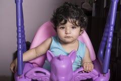 Retrato de um bebê pequeno no balanço do unicórnio, equipado fotos de stock royalty free