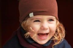 Retrato de um bebê de riso do bebê de um ano no revestimento e no lenço marrons do chapéu contra o fundo escuro em um dia morno d Imagens de Stock