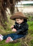 Retrato de um bebê de sorriso em um chapéu de vaqueiro e em um ja de couro fotografia de stock