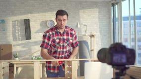 Retrato de um blogger do homem DIY em uma oficina, gravando um vídeo filme