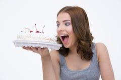 Retrato de um bolo bitting da mulher bonita Fotos de Stock