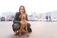 Retrato de um cão e de uma menina bonita no fundo de uma paisagem da cidade Caminhada em torno da cidade com um animal de estimaç fotos de stock royalty free