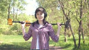 Retrato de um caçador de tesouro da menina com um detector de metais, olhando a câmera video estoque
