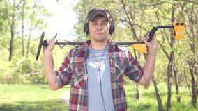 Retrato de um caçador de tesouro do homem com o detector de metais que olha a câmera vídeos de arquivo