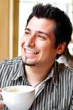 Retrato de um cappuccino bebendo feliz do homem novo imagem de stock royalty free