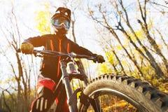 Retrato de um cavaleiro novo na proteção completa de uma máscara e de luvas do capacete da cara completa em uma bicicleta imagens de stock