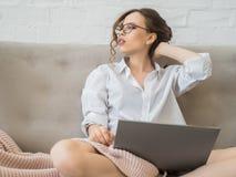 Retrato de um chá bebendo da jovem mulher feliz ao sentar-se em um sofá com laptop em casa Imagens de Stock Royalty Free