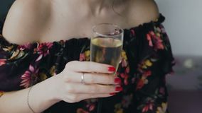 Retrato de um champanhe bebendo da menina encantador no banheiro A mulher bonita nova bebe o champanhe que relaxa em um quente filme