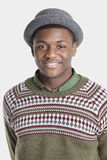 Retrato de um chapéu vestindo do homem afro-americano feliz sobre o fundo cinzento Imagem de Stock Royalty Free