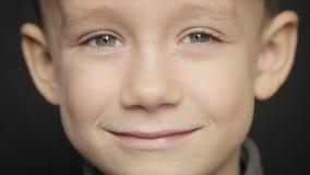 Retrato de um close-up do menino em um fundo preto Vídeo cheio de HD vídeos de arquivo
