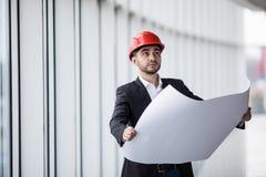 Retrato de um construtor do arquiteto que estuda o plano da construção, engenheiro civil sério da disposição que trabalha com ori Imagens de Stock Royalty Free