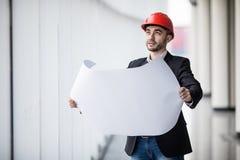 Retrato de um construtor do arquiteto que estuda o plano da construção, engenheiro civil sério da disposição que trabalha com ori Fotografia de Stock