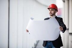 Retrato de um construtor do arquiteto que estuda o plano da construção, engenheiro civil sério da disposição que trabalha com ori Fotos de Stock