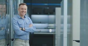 Retrato de um consultante perito profissional Smiles e de olhares na câmera como suportes na eletrônica brilhante, moderna video estoque