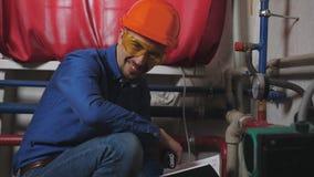 Retrato de um coordenador na sala de caldeira perto da tubulação e dos sensores Um homem em um capacete de segurança que sorri e  vídeos de arquivo