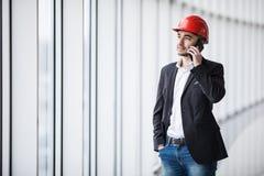 Retrato de um coordenador que fala no telefone contra janelas panorâmicos Imagem de Stock Royalty Free