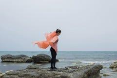 Retrato de um corredor das jovens mulheres que está com braços estendido em uma rocha do mar ao descansar após o exercício físico foto de stock royalty free