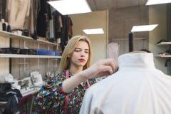 Retrato de um costureiro da menina que crie a roupa em seu próprio estúdio do projeto Desenhador de moda no trabalho fotografia de stock