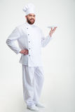 Retrato de um cozinheiro masculino feliz do cozinheiro chefe que está com placa Imagens de Stock
