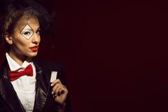 Retrato de um crouoier bonito novo da senhora em uma imagem do palhaço que esconde um cartão do ás fotografia de stock royalty free