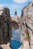Retrato de um curso extremo do plano para o ancião considerável na pedra do kjerag nas montanhas de Noruega, s fotografia de stock
