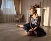 Retrato de um dançarino de bailado profissional que senta-se no assoalho de madeira fotografia de stock