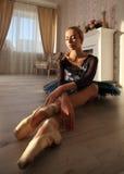 Retrato de um dançarino de bailado profissional que senta-se no assoalho de madeira Bailarina fêmea que tem um conceito do bailad fotos de stock royalty free