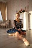 Retrato de um dançarino de bailado profissional que senta-se no assoalho de madeira Bailarina fêmea que tem um conceito do bailad foto de stock royalty free