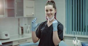 Retrato de um dentista ou de um auxílio novo do dentista que olham em linha reta à câmera e que guardam uma seringa cirúrgica filme