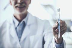 Retrato de um dentista superior de sorriso que guarda a escova de dentes no fundo seu paciente na clínica dental imagens de stock
