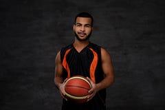 Retrato de um desportista afro-americano Jogador de basquetebol no sportswear com uma bola fotografia de stock