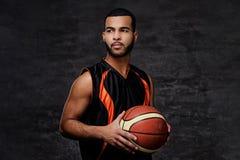 Retrato de um desportista afro-americano Jogador de basquetebol no sportswear com uma bola imagens de stock royalty free