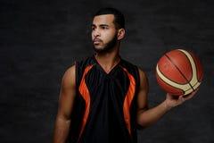 Retrato de um desportista afro-americano Jogador de basquetebol no sportswear com uma bola foto de stock royalty free