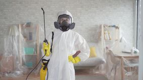 Retrato de um disinfector da jovem mulher ou de uma empresa de limpeza que olham na câmera