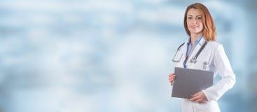 Retrato de um doutor bonito da mulher com a tabuleta sobre o backg azul fotografia de stock royalty free