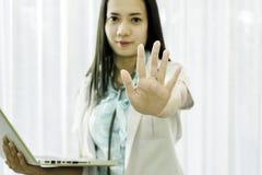 Retrato de um doutor fêmea em um uniforme branco que sorri e que guarda um portátil em sua mão ao levantar sua mão no hospital foto de stock