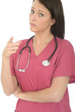 Retrato de um doutor fêmea novo interessado sério profissional bonito Pointing na decepção Foto de Stock Royalty Free