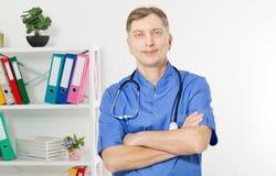 Retrato de um doutor maduro seguro Looking At Camera no fundo médico do escritório imagens de stock