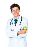 Retrato de um doutor masculino de sorriso que guarda a maçã verde no branco fotografia de stock royalty free
