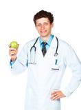 Retrato de um doutor masculino de sorriso que guarda a maçã verde no branco foto de stock